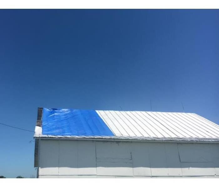 blue tarp on barn roof