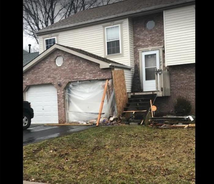 garage and side of home damaged by car