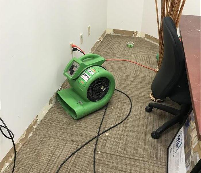 Medical Office with fan on carpet and baseboards removed